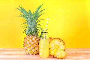 las-botellas-de-jugo-de-pina-con-fruta-de-pina-en-rodajas-en-la-mesa-de-madera_25381-49